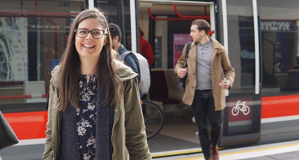 Woman smiles walking off tram