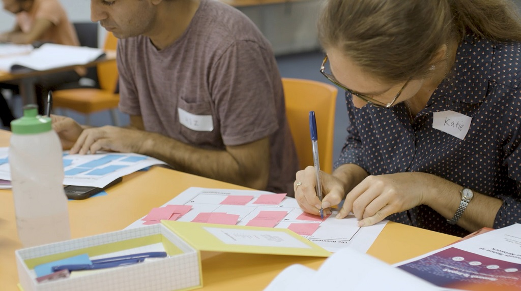 Researcher writes on canvas in workshop