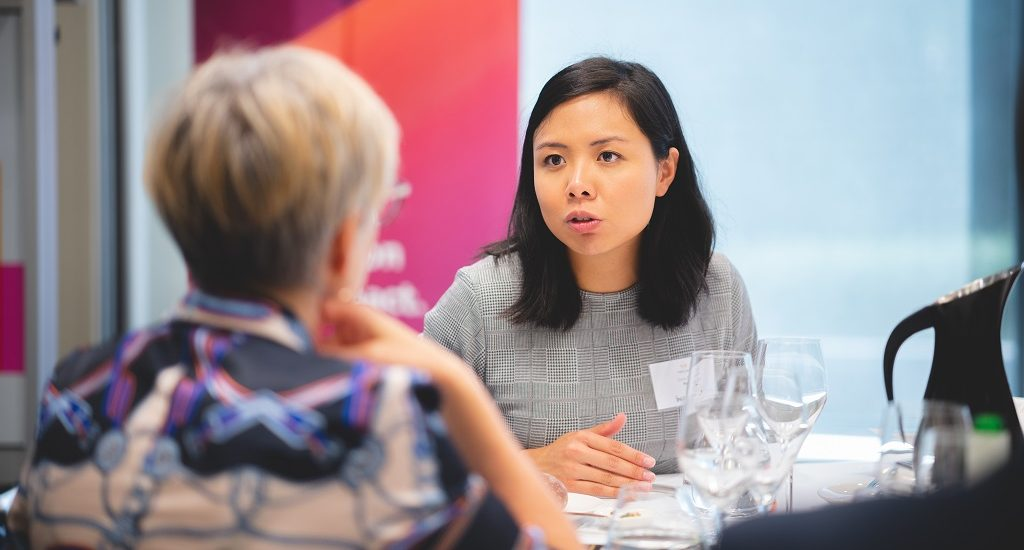 Entrepreneurs talk at a table in PwC Canberra